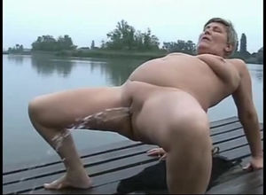 Grannie urinating near a lake
